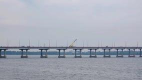 Guida di veicoli sul grande ponte concreto sopra il fiume in una città stock footage