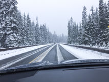 Guida di veicoli sulla strada nevosa innevata della montagna nella neve di inverno Punto di vista di punto di vista del ` s del d Immagini Stock