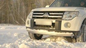 Guida di veicoli di Suv sul cumulo di neve alla strada di inverno sul movimento lento nevoso del fondo della foresta archivi video