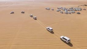 guida di veicoli di 4x4 SUVs attraverso le dune di sabbia nel deserto di Abu Dhabi azione Vista superiore su SUVs nel deserto Immagine Stock