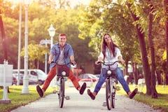 Guida divertente delle coppie di autunno felice sulla bicicletta immagini stock