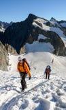 Guida e cliente della montagna che dirigono un ghiacciaio verso un'alta sommità alpina su una bella mattina di estate Immagini Stock