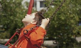 Guida felice del ragazzo su un'oscillazione Fotografia Stock