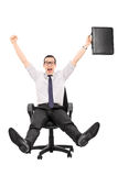 Guida felice dell'uomo d'affari in una sedia dell'ufficio Fotografia Stock