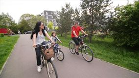 Guida felice della famiglia sulle loro bici al parco su Sunny Day Hanno insieme molto divertimento video d archivio