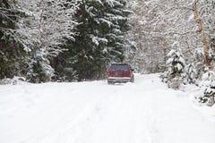 Guida fuori strada sulla strada nevosa della foresta di inverno Fotografie Stock