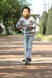 Guida giapponese del ragazzo su un motorino Fotografie Stock Libere da Diritti