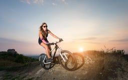 Guida graziosa della donna sulla bicicletta della montagna contro il cielo di sera Fotografie Stock Libere da Diritti
