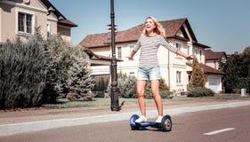Guida piacevole allegra della donna sul motorino e sull'esultanza di equilibrio fotografie stock