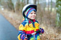 Guida prescolare sveglia del ragazzo del bambino sul motorino in parco Immagini Stock Libere da Diritti