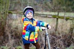 Guida prescolare sveglia del ragazzo del bambino sul motorino in parco Fotografia Stock Libera da Diritti