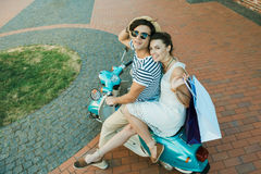 Guida sorridente delle coppie sui sacchetti della spesa della tenuta e del motorino all'aperto Fotografia Stock Libera da Diritti