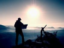 Guida turistica alta che guarda nella mappa di carta Natura collinosa selvaggia Fotografia Stock
