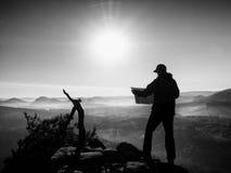 Guida turistica alta che guarda nella mappa di carta Natura collinosa selvaggia Fotografie Stock