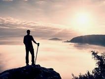Guida turistica alta su roccia con il palo a disposizione Viandante con attrezzatura sportiva Fotografia Stock Libera da Diritti