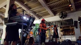 Guidance Band singing and jams on stage at Mai Tai Bar. Honolulu -  May 11, 2016: Guidance Band, singing and jams on stage at Mai Tai Bar in Ala Moana Shopping stock photo