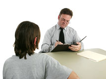 Guidance Counselor - Taking Notes. A guidance counselor interviewing a teen and taking notes stock photo