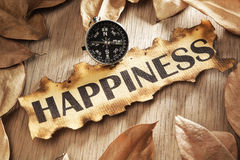 Guidance to happiness concept. Guidance and key to happiness concept using printed word on burnt paper along with compass, surrounded by dry leaf royalty free stock photography