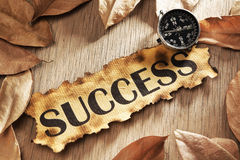 Guidance to success concept. Using printed word on burnt paper along with compass, surrounded by dry leaf royalty free stock photography
