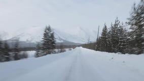 Guidando attraverso la foresta di inverno sulla strada nevosa stock footage