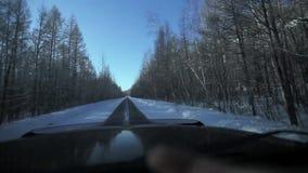 Guidando attraverso la foresta di inverno sulla strada nevosa video d archivio