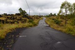 Guidando attraverso la strada della cresta della caldera fra la vista del cratere estinto del vulcano Batur fotografia stock