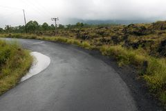 Guidando attraverso la strada della cresta della caldera fra la vista del cratere estinto del vulcano Batur fotografie stock libere da diritti