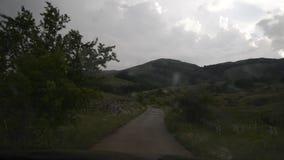 Guidando giù la collina un giorno piovoso dentro un'automobile video d archivio