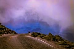 Guidando giù la montagna sotto il cielo grigio fotografie stock