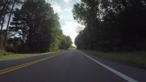 Guidando giù la strada campestre a due corsie espone al sole il talento stock footage