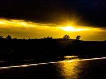 Guidando nel tramonto dopo la pioggia immagini stock libere da diritti
