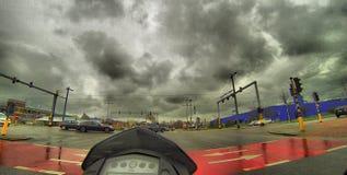 Guidando sopra un'intersezione occupata nella città su un motociclo Fotografie Stock