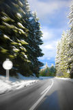 Guidando su una strada della montagna in neve immagini stock libere da diritti