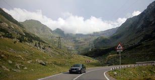 Guidando su una strada delle alte montagne Immagini Stock