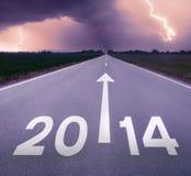 Guidando su una strada vuota verso 2014 tempestoso imminente Immagine Stock