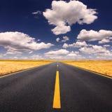Guidando sulla strada asfaltata al giorno soleggiato adorabile Immagine Stock