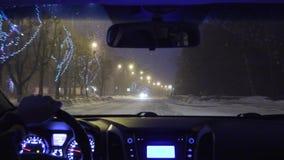 Guidando in un'automobile nella città di notte nell'inverno vista dalla carrozza stock footage