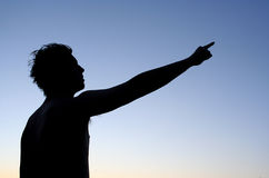 Guide. Silhouette of man pointing at something far away Royalty Free Stock Photography