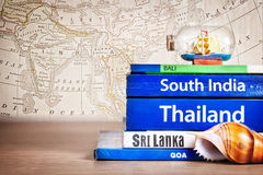 Guide books with ship. Guide books on the table with Seashell and ship in the bottle on its at old map background. Books with titles: South India, Bali, Sri stock photo