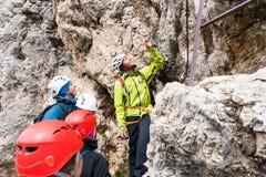 Guide de montagne instruisant de jeunes grimpeurs au début d'un raide par l'intermédiaire du ferrata dans les dolomites photos stock