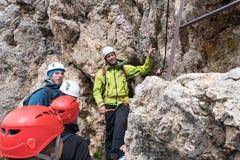 Guide de montagne instruisant de jeunes grimpeurs au début d'un raide par l'intermédiaire du ferrata dans les dolomites photo stock