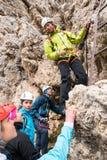Guide de montagne instruisant de jeunes grimpeurs au début d'un raide par l'intermédiaire du ferrata dans les dolomites photo libre de droits
