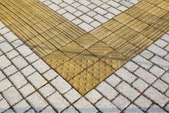 Guide del marciapiede per i ciechi Ciottoli concreti gialli sul passaggio pedonale per la gente di cecità immagini stock libere da diritti