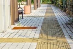Guide del marciapiede per i ciechi Ciottoli concreti gialli sul passaggio pedonale per la gente di cecità fotografia stock