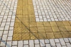 Guide del marciapiede per i ciechi Ciottoli concreti gialli sul passaggio pedonale per la gente di cecità immagini stock