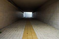 Guide del marciapiede per i ciechi Ciottoli concreti gialli sul passaggio pedonale per la gente di cecità nel tunnel sotterraneo fotografie stock libere da diritti