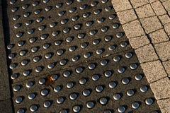 Guide del marciapiede per i ciechi Ciottoli concreti sul passaggio pedonale per la gente di cecità fotografia stock libera da diritti