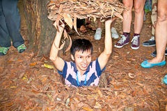 A guide demonstrating how a Vietcong hide into the Tunnel. CU CHI, VIETNAM - NOV 17: A guide demonstrating how a Vietcong hide into the Tunnel on Nov 17 2013. Cu Royalty Free Stock Image