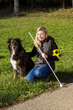 Guide dog. A guide dog sitting next to a blind woman on a meadow royalty free stock photos
