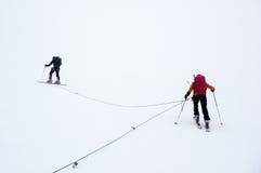 Guide et clients de montagne sur un glacier pendant un blanc dehors Images stock